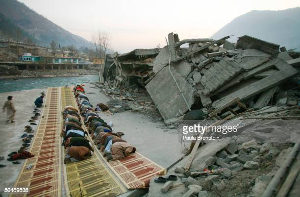 Pakistani men pray near the rubble of a destroyed mosque December 19 2005 in Balakot Pakistan Lack of snow is giving survivors of the October 8 quake...