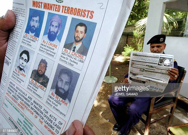Pakistani men read newspapers carrying advertisements on their front pages offering rewards totalling 11 million dollars for information on six...