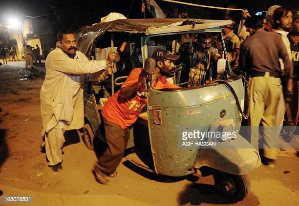 Pakistani men remove an auto rickshaw from the site of twin bomb blasts near the secular Muttahida Qaumi Movement party office in Karachi on May 4...