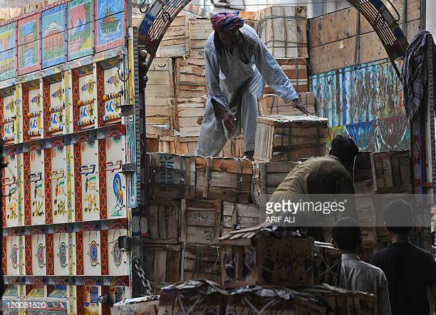 Pakistani men remove mango boxes from a truck at a vegetable market in Lahore on July 28 2011 Pakistani government statements that tax receipts fell...