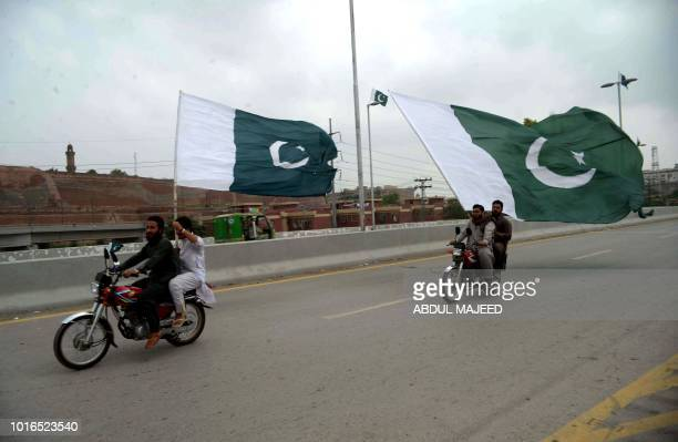 Pakistani men ride on bikes along a road with Pakistan's national flags as they celebrate the country's Independence Day in Peshawar on August 14...