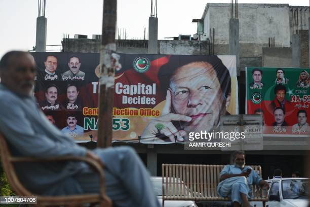 Pakistani men sit near a poster of Pakistan's cricketer-turned politician and head of the Pakistan Tehreek-e-Insaf party Imran Khan, in Islamabad on...