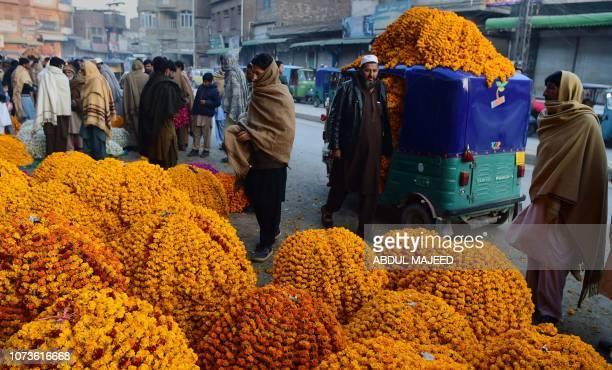 Pakistani men stand around piles of marigold flower bundles at a flower market on the outskirts of Peshawar on December 15 2018