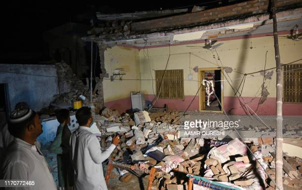 Pakistani men stand beside a collapsed building following an earthquake on the outskirts of Mirpur on September 24 2019 At least 19 people have been...