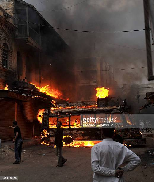 Pakistani men stand in front of burning bus which was set alight by angry protesters after the bomb blast during the Shiite religious procession on...