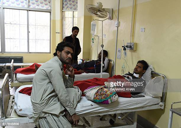 Pakistani men take care of an injured relative at a hospital in Quetta on October 25 after an overnight militant attack on the Police Training...