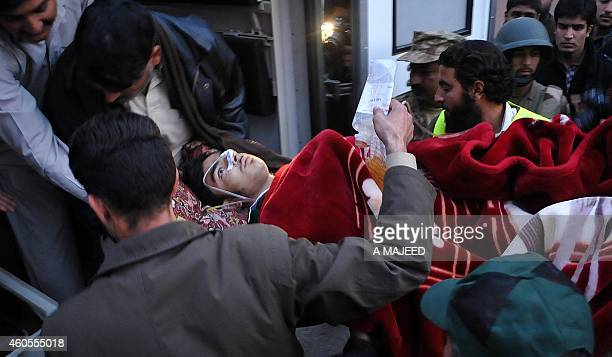 Pakistani men transport a wounded student to hospital after Taliban gunmen attacked a school in Peshawar on December 16 2014 Taliban insurgents...