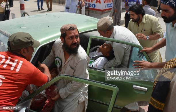 TOPSHOT Pakistani men transport injured blast victims at a hospital after a suicide attack near a polling station in Quetta on July 25 2018 At least...