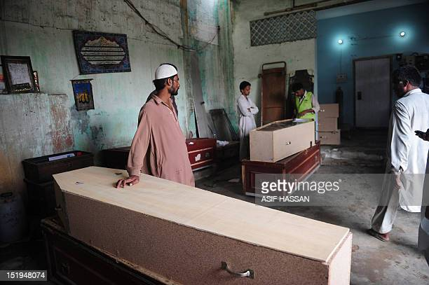 Pakistani men wait alongside coffins for the bodies of their relatives who died in a garment factory fire at the EDHI Morgue in Karachi on September...