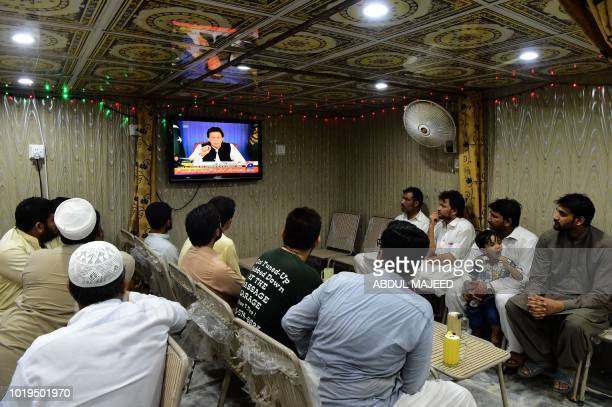 Pakistani men watch a television broadcasting the speech of newly appointed Pakistani Prime Minister Imran Khan as he addresses the nation at a...
