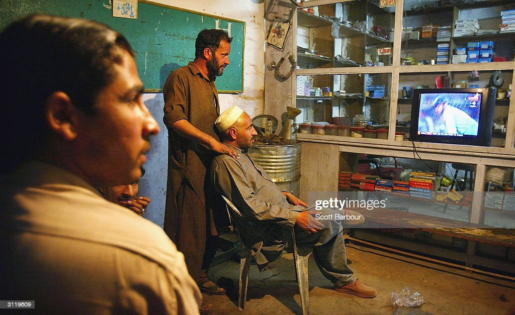 Pakistani men watch the fourth Pakistan v India one day international match on television March 21 2004 in Rawalpindi Pakistan Cricket fever has...