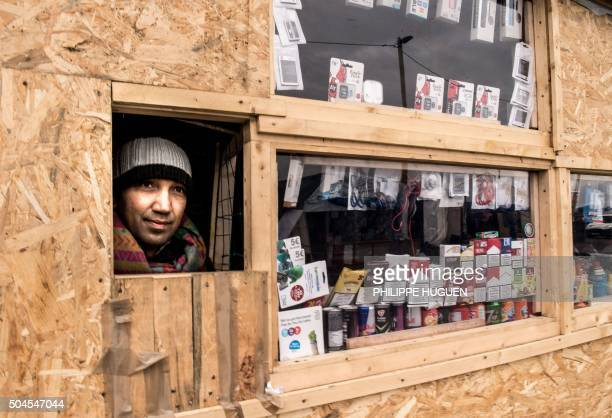 Pakistani migrant looks out of his shop setup at the migrants' camp known as the 'Jungle' on January 11 in the northern French port city of Calais...