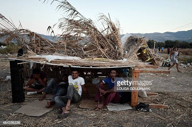 Pakistani migrants sit in their makeshift shelter on August 16 outside the abandoned Captain Elias hotel on the Greek Aegean island of Kos where...