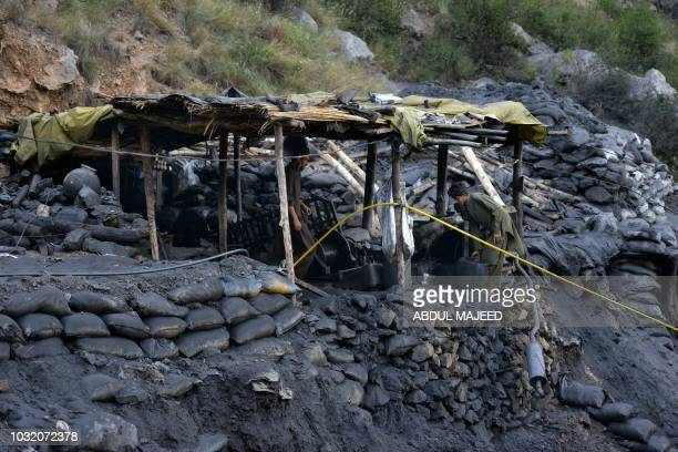 Pakistani miners carry on repair works after a coal mine collapsed in Akhurwal village near Darra Adam Khel town on September 12 2018 Nine miners...
