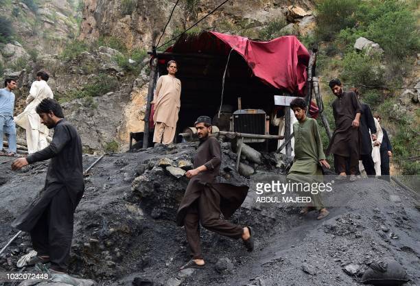 Pakistani miners walks near the collapsed coal mine in Akhurwal village near Darra Adam Khel town on September 12 2018 Nine miners were killed and...