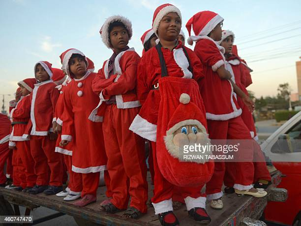 Pakistani minority Christian children dressed as Santa Claus pose during a Christmas peace rally in solidarity of the victims of the Peshawar school...