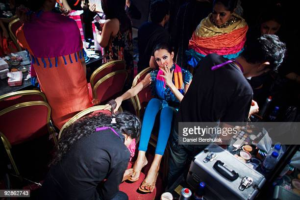 Pakistani model Nadia Hussain wearing a creation by Pakistani designer Maheen Hussain sits as she has her toenails blow dried backstage during the...