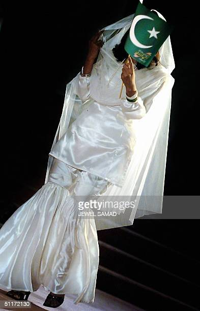 Pakistani model presents an outfit designed by Amna Malik one of the top Pakistani fashion designer while waving a national flag during a fashion...