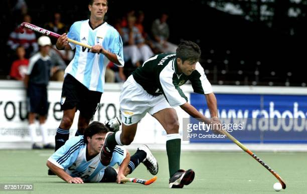 Pakistani Mohammad Saqlain passes Matias Vila from Argentina 17 August 2003 during the game Pakistan vs Argentina at the Champions Trophy Fieldhockey...