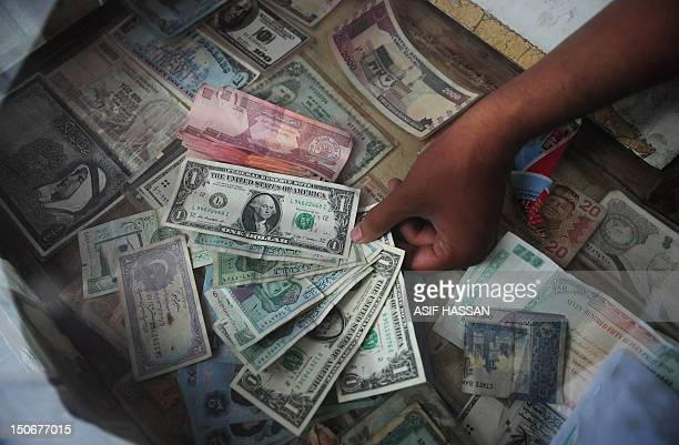 A Pakistani money exchange dealer displays foreign currency notes at his roadside stall in Karachi on August 24 2012 The Pakistani rupee sank to an...