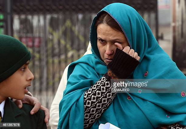 A Pakistani mother cries as she leaves the Army Public School with her children after it was reopened following an attack there by Taliban militants...