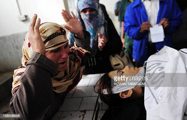 A Pakistani mother mourns beside the body of her daughter who was killed while on the job as a polio vaccination worker at a hospital following an...