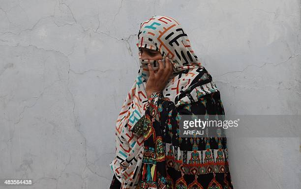 A Pakistani mother whose children were sexually abused by a gang looks on as she and others gather at a house in the village of Hussain Khanwala in...