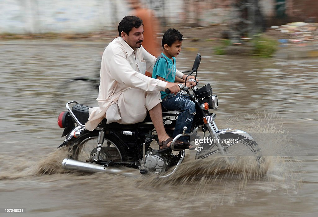 A Pakistani motorcyclist crosses a flooded street following heavy rain in Peshawar on April 26, 2013. Pakistan has suffered devastating monsoon floods for the last three years, including the worst in its history in 2010 when catastrophic inundations killed almost 1,800 people and affected 21 million.
