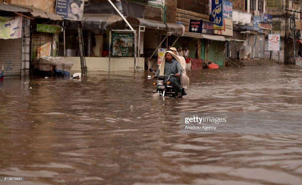 Pakistani motorcyclist drives through a flooded street after heavy monsoon rains hit Rawalpindi province of Pakistan on July 13 2017 Heavy monsoon...