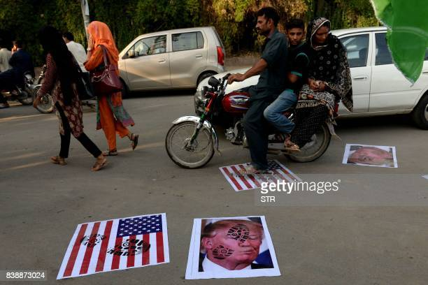 A Pakistani motorcyclist rides over images of US President Donald Trump and a US flag on a street in Lahore on August 25 2017 Angry and offended...