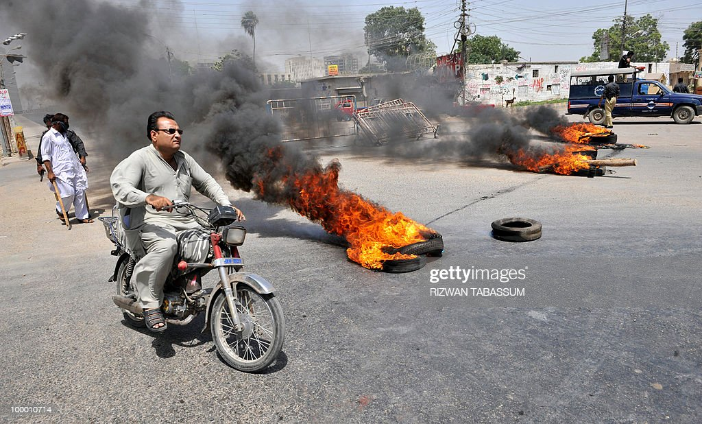 A Pakistani motorcyclist rides past burning tyres burning tyres torched by an angry mob during a protest against alleged target killings in Karachi on May 20, 2010. At least 17 people including two children have been killed in political clashes in Pakistan's financial capital Karachi in the past two days, a government official and police said. Police and paramilitary have been put on high alert and authorities closed all schools and colleges after the latest outbreak of politically related violence in Karachi, the biggest and richest city in Pakistan.