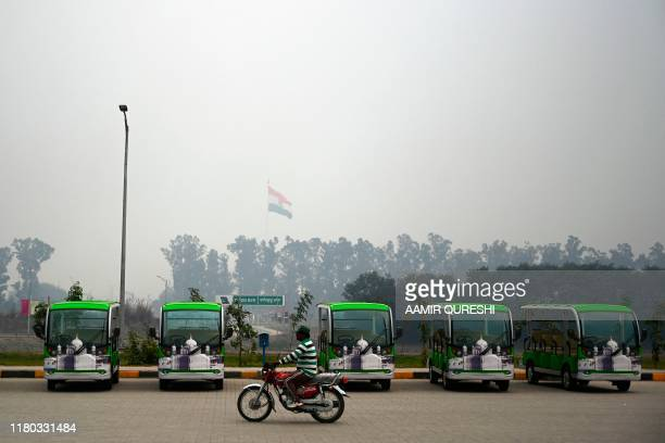 A Pakistani motorcyclist rides past golf carts which are for Sikh pilgrims at the immigration center ahead of the opening site near the Shrine of...