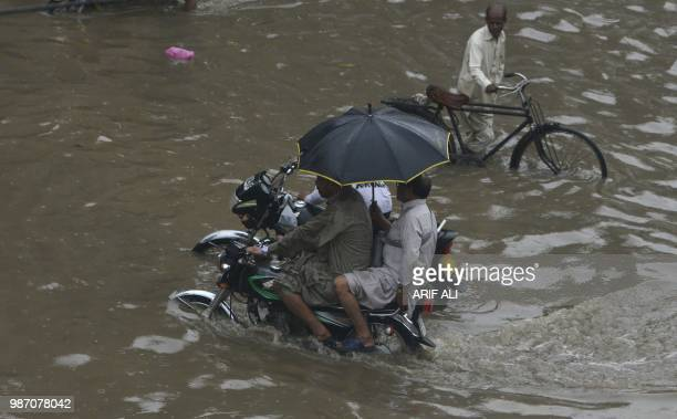 TOPSHOT Pakistani motorcyclists ride through a flooded street after heavy rains in Lahore on June 29 2018