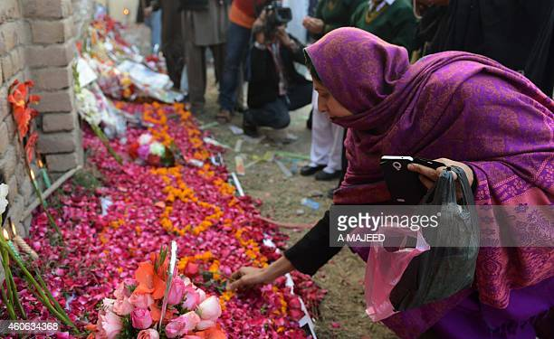 A Pakistani mourner lays flowers outside an armyrun school that was attacked by Taliban militants in Peshawar on December 18 2014 Pakistan is...