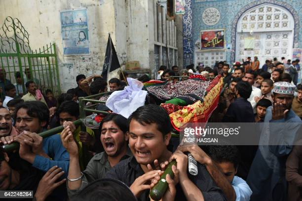 Pakistani mourners carry the coffin of a blast victim during his funeral in the town of Sehwan in Sindh province some 200 kilometres northeast of the...