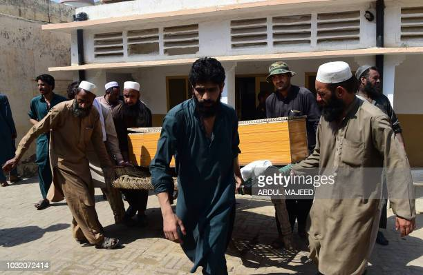 Pakistani mourners carry the coffin of a miner killed during the collapsing of coal mine in Darra Adam Khel town on September 12 2018 Nine miners...