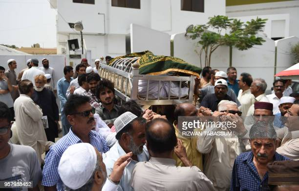 Pakistani mourners carry the coffin of hockey player Mansoor Ahmed during his funeral in Karachi on May 13 2017 Pakistan's World Cupwinning hockey...