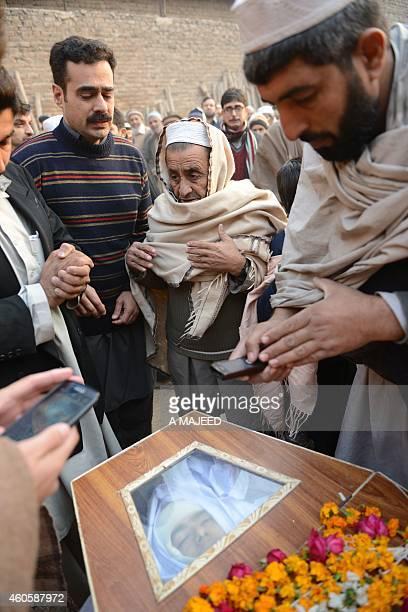 Pakistani mourners gather around a coffin during the funeral ceremony for victims of an attack by Taliban militants at an armyrun school in Peshawar...