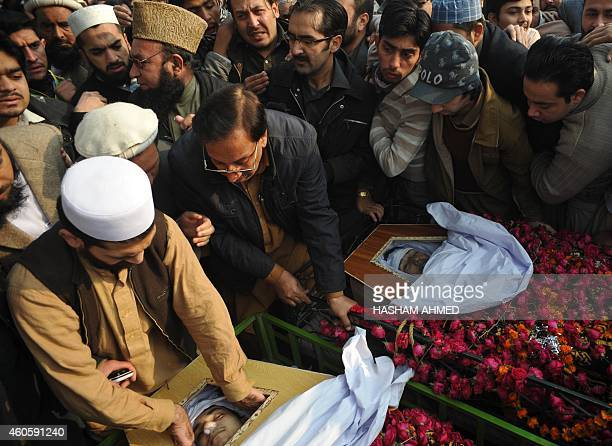 Pakistani mourners gather around coffin during a funeral ceremony a day after an attack on an armyrun school by Taliban militants in Peshawar on...