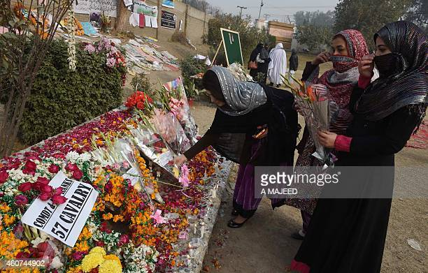 Pakistani mourners leave bouquets as they pay their respects outside the armyrun school where 149 people were massacred by the Taliban in Peshawar on...