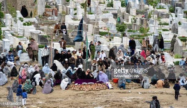 Pakistani mourners of the Shia Hazara ethnic minority gather around graves of the victims as they sitin during a protest in Quetta on April 15...