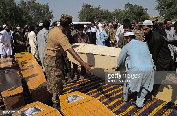 Pakistani mourners place coffins on the ground before funeral prayers for the miners killed in collapsed coal mine accident in Darra Adam Khel town...