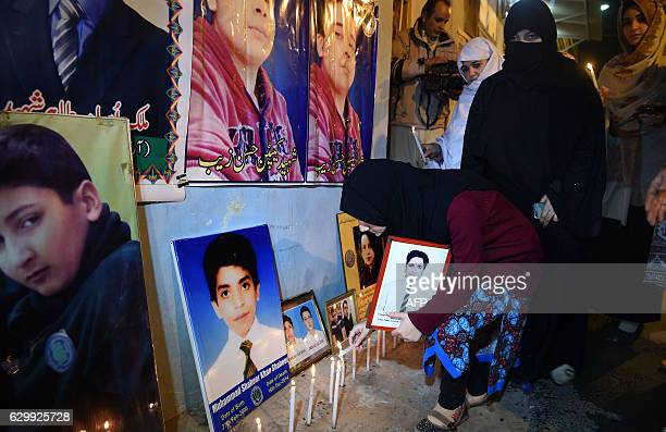 Pakistani mourners place lighted candles beside a display of photographs in Peshawar on December 15 during a ceremony marking the second anniversary...