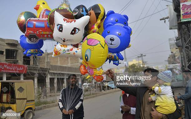 Pakistani Muslim buys balloons from a vendor after attending a religious ceremony commemorating the birth of Muslims' beloved Prophet Muhammed known...