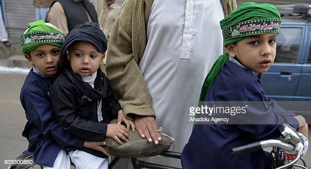Pakistani Muslim children hold religious flags as they attend a religious ceremony commemorating the birth of Muslims' beloved Prophet Muhammed known...