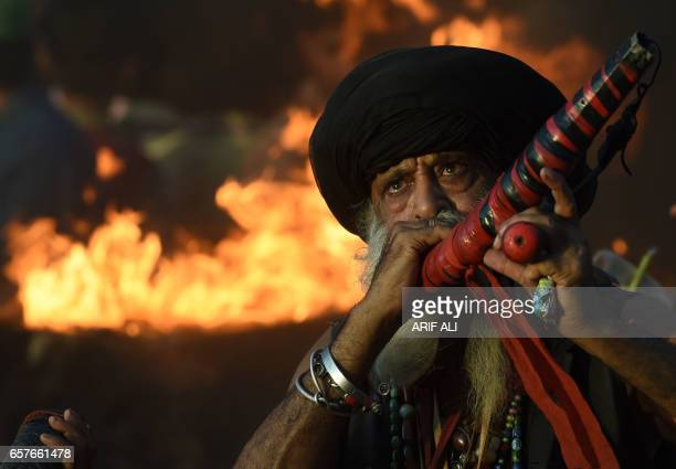Pakistani Muslim devotee blows a horn at the shrine of Muslim Sufi saint Shah Hussain popularly known as Madho Lal Hussain during the three days...