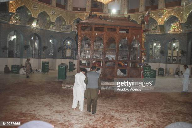 Pakistani Muslim devotees and security forces are seen following a suicide attack at the 13th century old shrine of a Muslim saint in the town of...