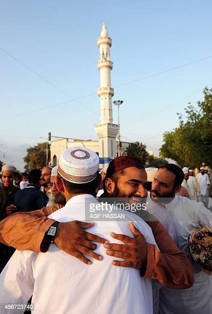 Pakistani Muslim devotees greet each other after offering Eid alAdha prayers outside a mosque in Karachi on October 6 2014 Muslims across the world...