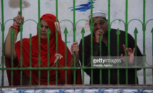 Pakistani Muslim devotees look at the shrine from a fence a day after a suicide attack at the 13th century old shrine of a Muslim saint in the town...