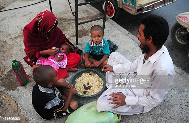 A Pakistani Muslim family waits to break their fast during the holy fasting month of Ramadan on a street in Karachi on July 2 2014 The fasting month...
